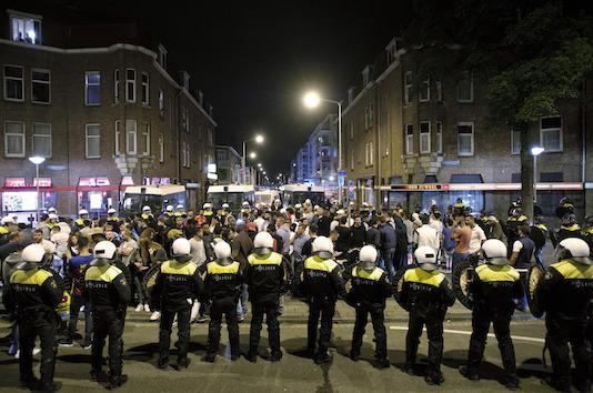 1899-12-30 00:00:00 DEN HAAG - Leden van de Mobiele Eenheid (ME) vormen een linie om mensen in te sluiten op het Hobbemaplein in de Haagse Schilderswijk. Hier gold een samenscholingsverbod, nadat drie dagen op rij rellen zijn uitgebroken. Ongeveer honderd mensen werden gearresteerd. Betogers gingen de straat op naar aanleiding van de dood van Mitch Henriquez, die stikte en stierf door toedoen van de agenten die hem arresteerden. ANP MARTEN VAN DIJL