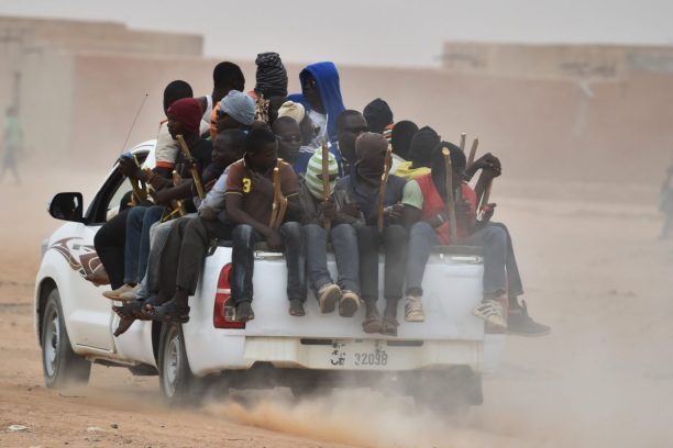 2015-06-01 16:50:00 A pick-up truck carrying migrants in its cargo bed rides in Agadez on June 1, 2015, en route to Libya, as the migrants attempt to reach Europe. The passengers hold on to sticks attached to the truck, to not fall off while riding in the desert.  AFP PHOTO / ISSOUF SANOGO