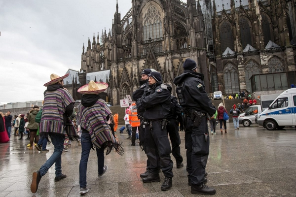 2016-02-08 00:00:00 epa05149546 Police officers stand next to carnival revellers who celebrate despite the rain in Cologne, Germany, 08 February 2016. The carnival's procession for Rose Monday went ahead in Cologne despite the parade in neighboring Duesseldorf being cancelled due to stormy weather.  EPA/MAJA HITIJ