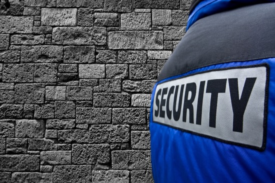 rear view at security guard next to grey wall