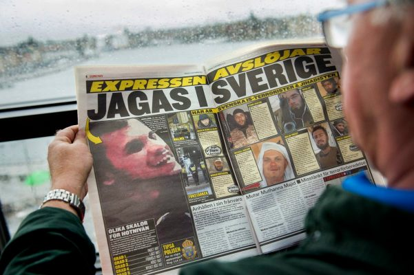 2015-11-19 14:30:57 epa05032597 A man reads a newspaper in Stockholm, Sweden, 19 November 2015 displaying a grainy photograph of a man believed to be suspected of planning terror crimes in Sweden as stated by Swedish authorities published in the evening daily Expressen. Swedish media have published the photo of the alleged suspect, reporting that he has fought alongside 'Isis' in Syria.  EPA/MARCUS ERICSSON